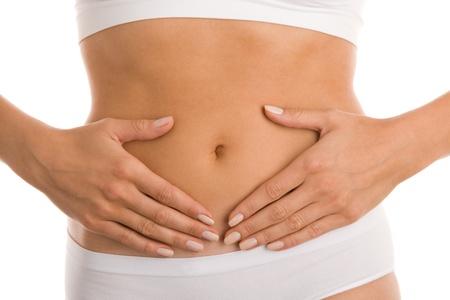 flat stomach: Donna tocca il suo addome