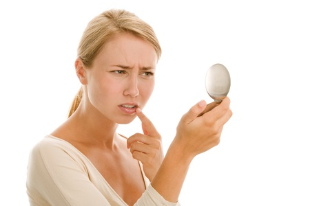 Young woman examining face in mirror