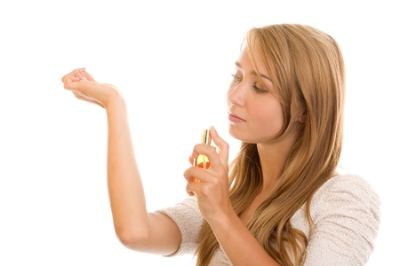 Young woman spraying perfume on wrist photo