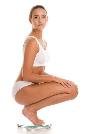 dieting: Jonge vrouw, gehurkt op de badkamer schaal