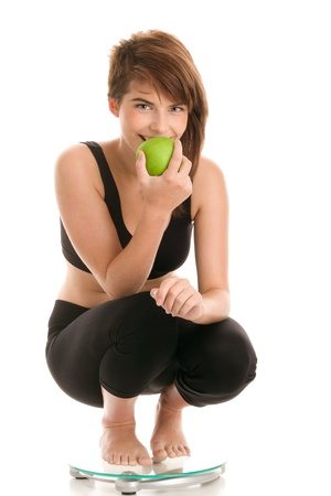 Young woman crouching on bathroom scale eating apple Stock Photo