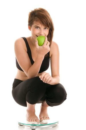 Young woman crouching on bathroom scale eating apple Banco de Imagens
