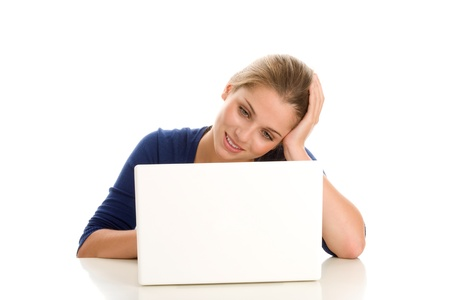 Young woman using laptop computer at desk photo