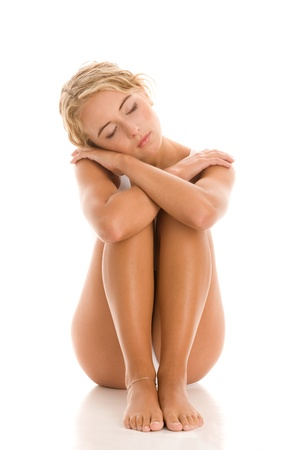 legs crossed at knee: Young woman sitting hugging her knees Stock Photo