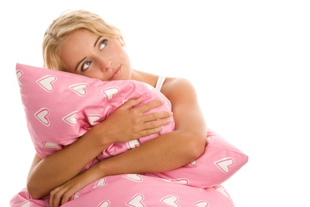 Young woman lying on bed with pink pillow