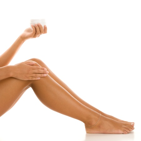 Woman rubbing lotion on her legs Stock Photo - 15913927