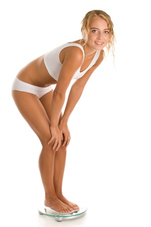 knee bend: Young woman standing on scale Stock Photo