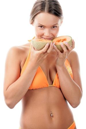 Woman in bikini eating cantaloupe melon photo