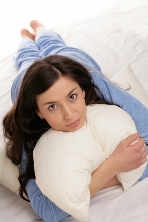 Woman lying on bed with pillow Stock Photo - 16732595