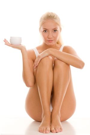 belles jambes: Jeune femme avec pot de crème de beauté Banque d'images