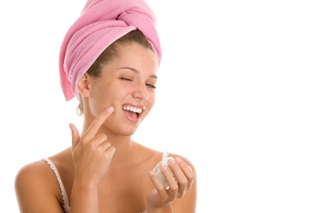 Young woman applying beauty cream photo