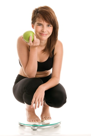Young woman in underwear crouching on bathroom scale holding green apple photo