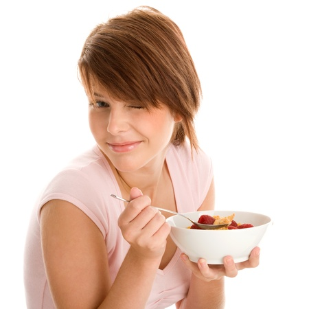 Pretty woman eating corn flakes with fruits