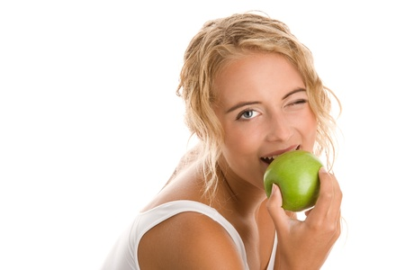 winking: Young blonde woman eating green apple