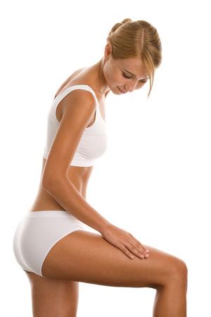 Woman in white underwear massaging her thigh Stock Photo