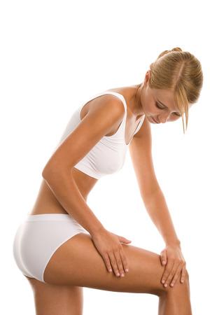 mujer celulitis: Mujer joven en ropa interior blanca que da masajes a su pierna Foto de archivo