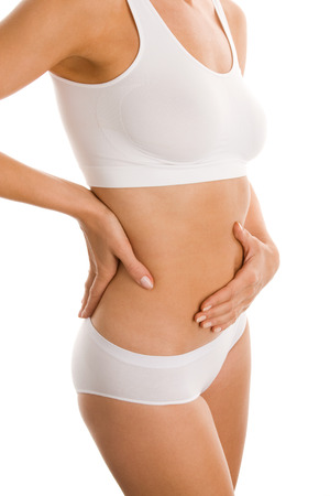 Young woman massaging her belly photo
