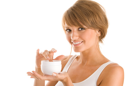 Young woman getting body lotion out of jar photo