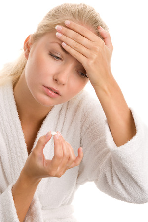 unhealthiness: Young woman with headache taking pill
