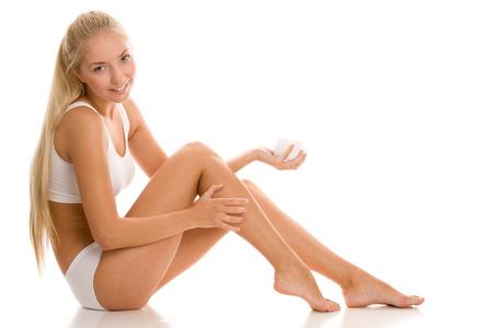 belles jambes: Jeune femme d'appliquer la crème sur ses jambes