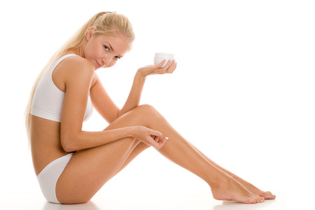 Young woman applying lotion to her legs