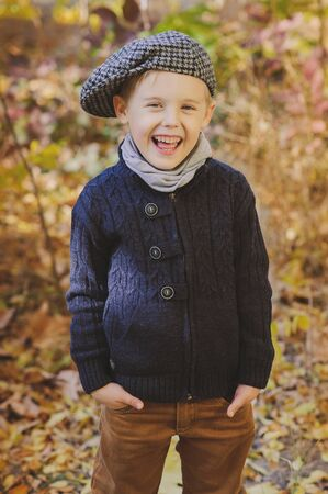 funny boy: Funny boy in hat and scarf is smiling outdoor in autumn. Yellow  foliage. Stock Photo