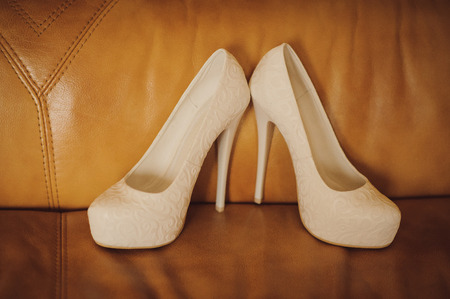 attribute: Attribute bride. Wedding high-heeled shoes on brown sofa Stock Photo