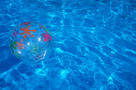 Beach ball floating in a blue swimming pool. Summer background. Banco de Imagens