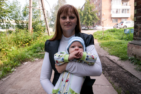 mom with a baby in her arms in the summer on the street