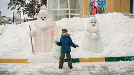 boy and snow figures of Santa Claus and snow Maiden Banco de Imagens