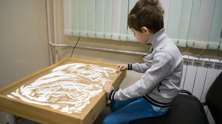 enfant dans la thérapie de sable en classe Banque d'images