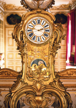 versailles: Versailles, France - 10 August 2014 : Vintage mechanical gold clock at Versailles Palace ( Chateau de Versailles ).