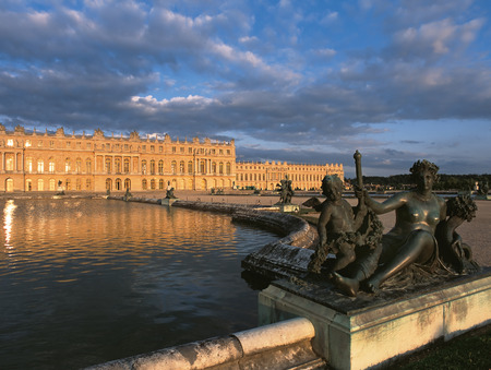 queen bed: Versailles, France - 13 August 2014 : Bronze statue and exterior view of Versailles Palace ( Chateau de Versailles ) at sunset. Editorial