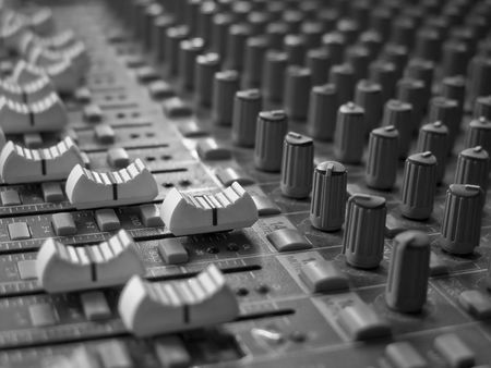 Close up image of an analog audio mixing board with several channels and push buttons visible. Dials and volume levels are also visible.  Stock Photo - 4579640