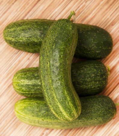 fresh cucumbers on a wooden background photo