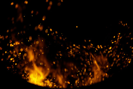 wood and fire: sparks of fire on a black background Stock Photo