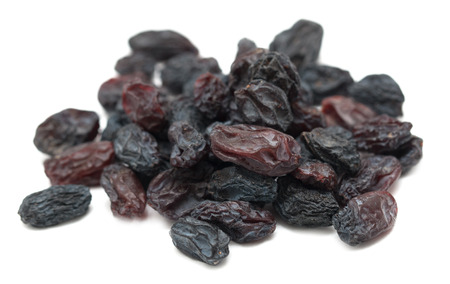 Black dried grapes on a white background Stock Photo