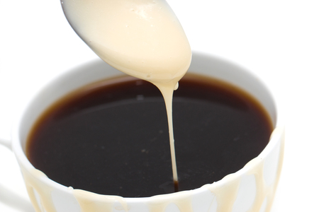 condensed: cup of coffee with condensed milk on a white background