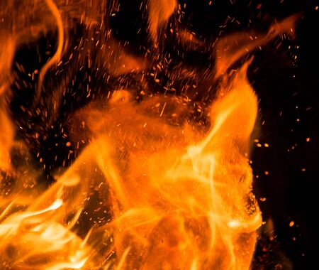 orange inferno: fire flames with sparks on a black background Stock Photo