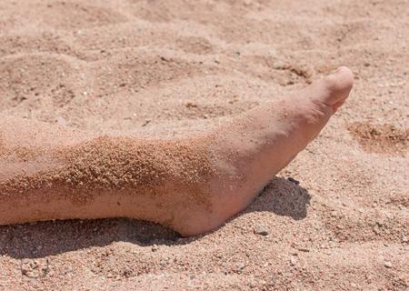 feet in the sand on the beach