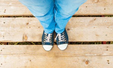 legs in sneakers on a wooden floor Stock Photo