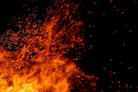 Feuerflamme mit Funken auf einem schwarzen Hintergrund