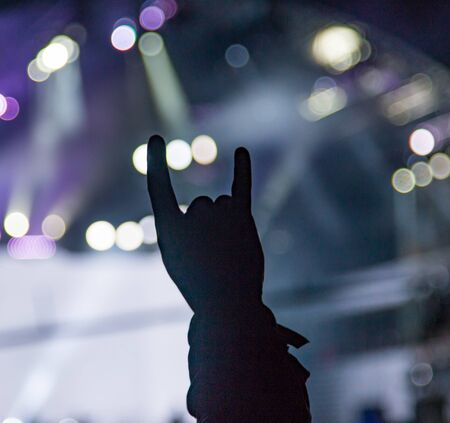 silhouettes of hands by spotlights at a concert