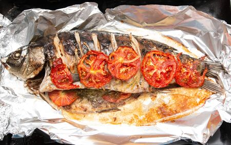 baked fish in foil Фото со стока