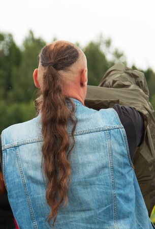 man with long hair gathered in ponytail Фото со стока
