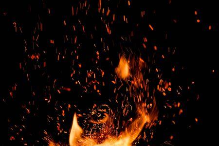 Feuerflamme mit Funken auf einem schwarzen Hintergrund Standard-Bild