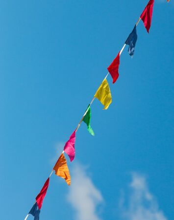 multi-colored flags against a blue sky