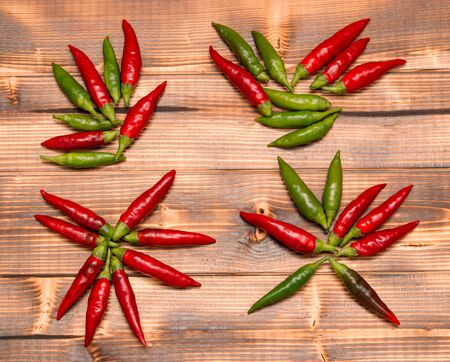 red green chili peppers on wooden background