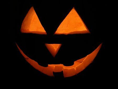 Night shot of carved pumpkin lit for Halloween.