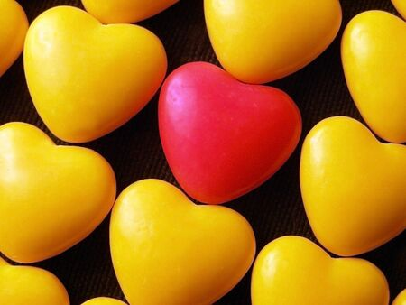 Pink candy heart surrounded by yellow hearts.